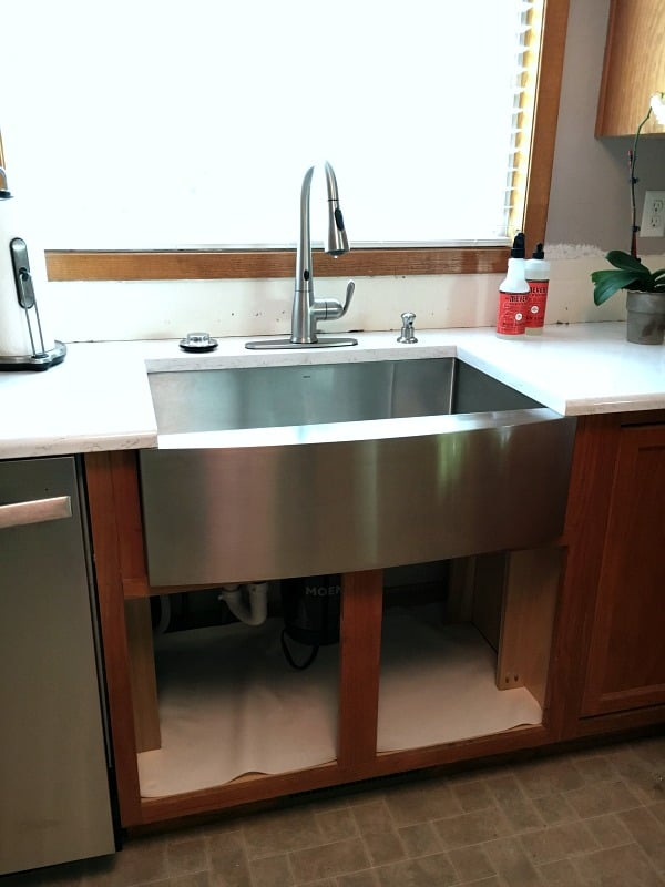 the updated sink area with moen garbage disposal, faucet and apron sink