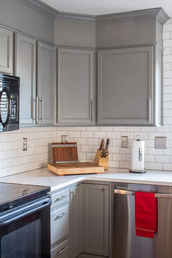 A builder grade kitchen gets a new look with classic features like gray cabinets, Quartz counters and subway tile. Love the pop of red!
