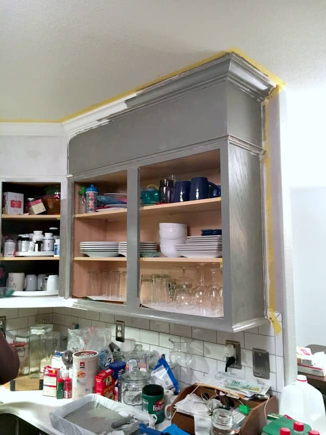 how to easily paint kitchen cabinets - primed cabinet frames with first coat of paint