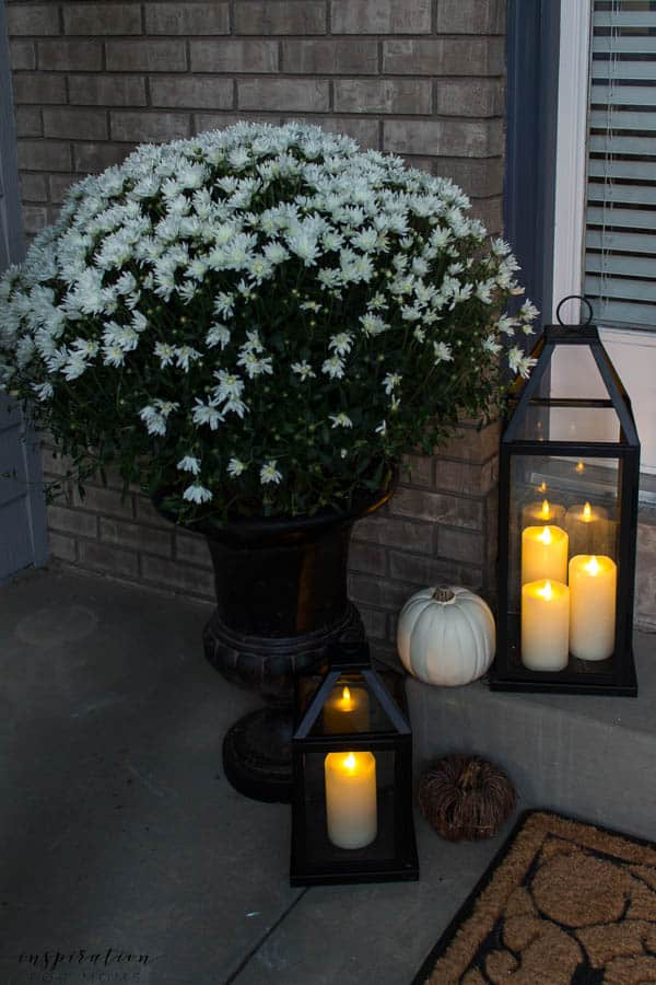 Welcome to a neutral Fall home tour with white pumpkins and plenty of cozy touches. fall porch, fall pillow, white mums, black lanterns