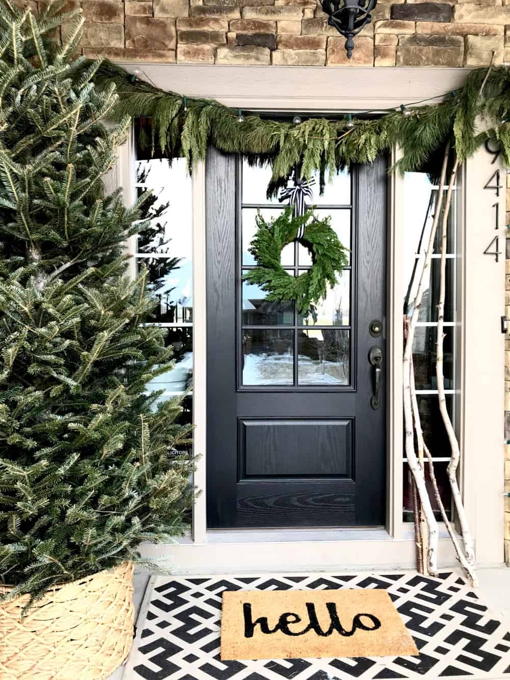 Love this Winter porch with a giant tree and all the black and white decor.