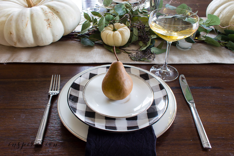 thanksgiving tablescape with white pumpkins, eucalyptus, buffalo check plates and champagne