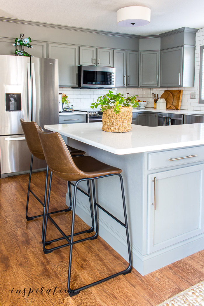Gorgeous clean kitchen with leather bar stools, gray cabinets and subway tile.
