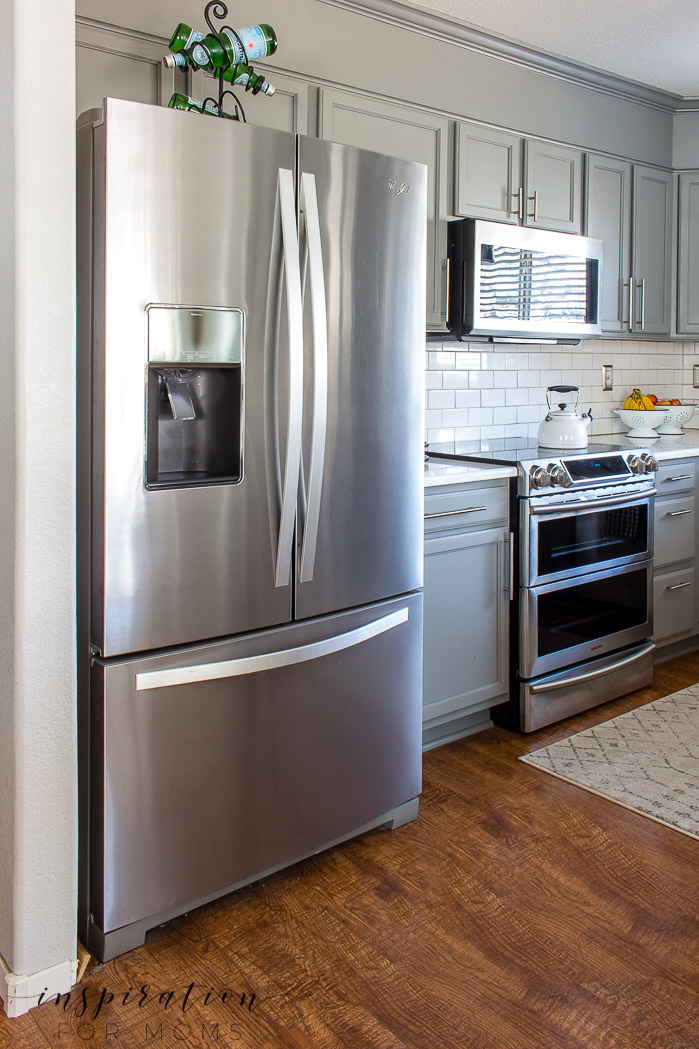 Gorgeous clean kitchen with stainless steel appliances, gray cabinets and subway tile.