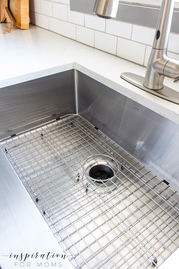 clean stainless steel farmhouse sink with metal grid