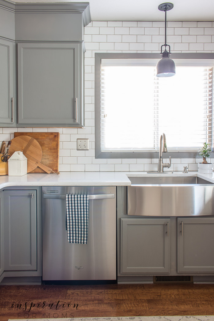 Gorgeous clean kitchen with wood floors, gray cabinets, farmhouse sink and subway tile.