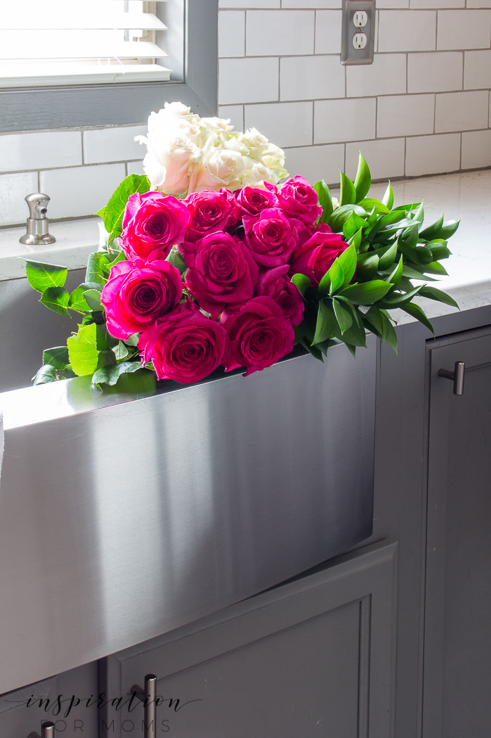 Decorating with hints of green is easy to do with the help of fresh flowers and pretty plants. farmhouse sink with roses, Quartz counters modern kitchen