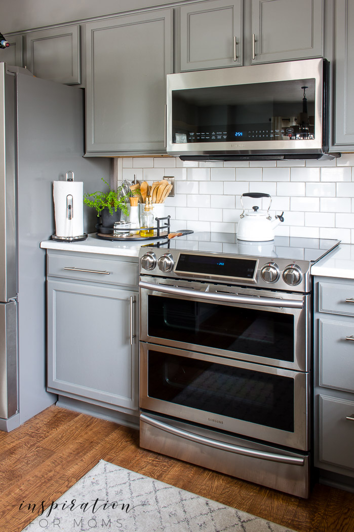 Decorating with hints of green is easy to do with the help of fresh flowers and pretty plants. white subway tile, stainless steel appliances, Quartz counters modern kitchen
