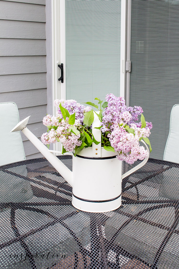 water can on patio table filled with lilacs