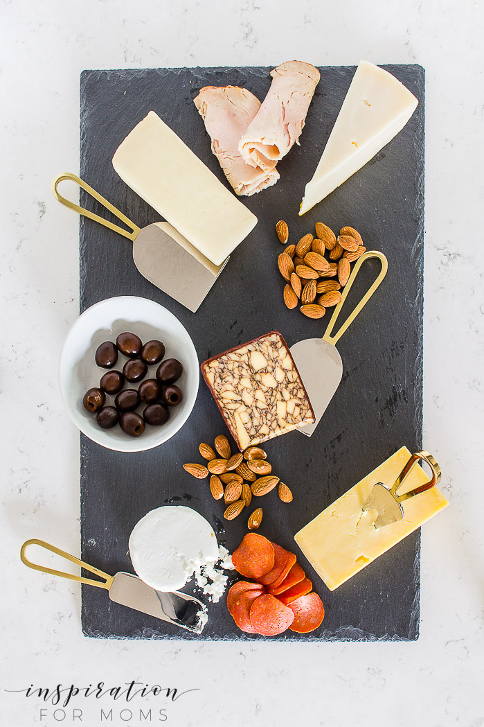Entertain friends and family easily this summer with a fun charcuterie board. cheese on slate board