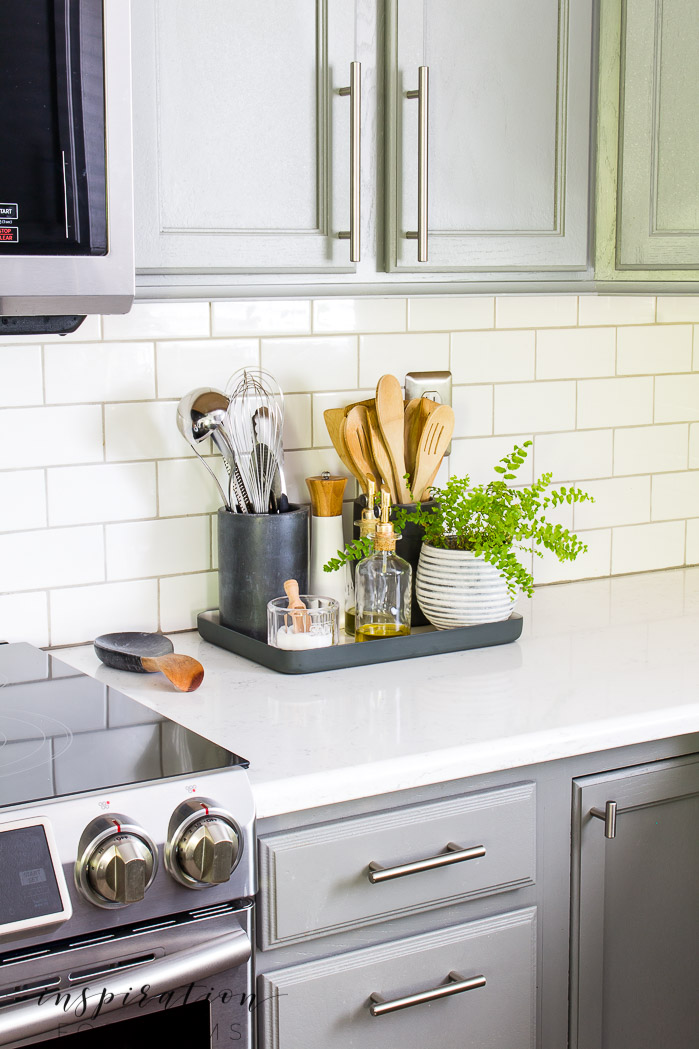 kitchen organization tray with oil bottles and crocks with utensils
