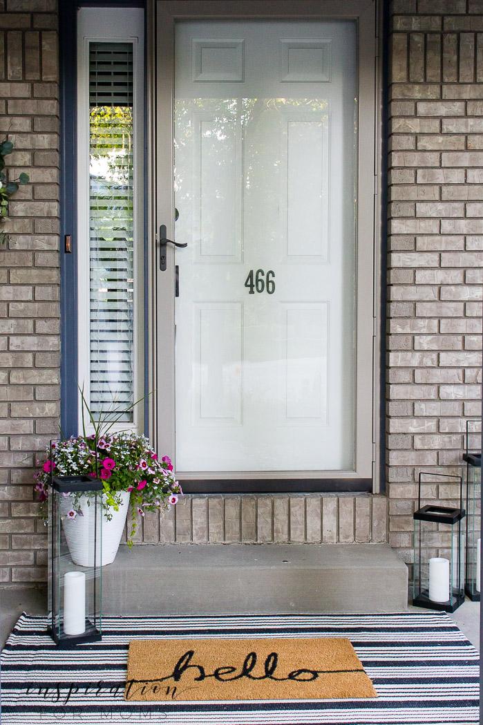 front door with layered door mat rug combo, lanterns, summer flowers