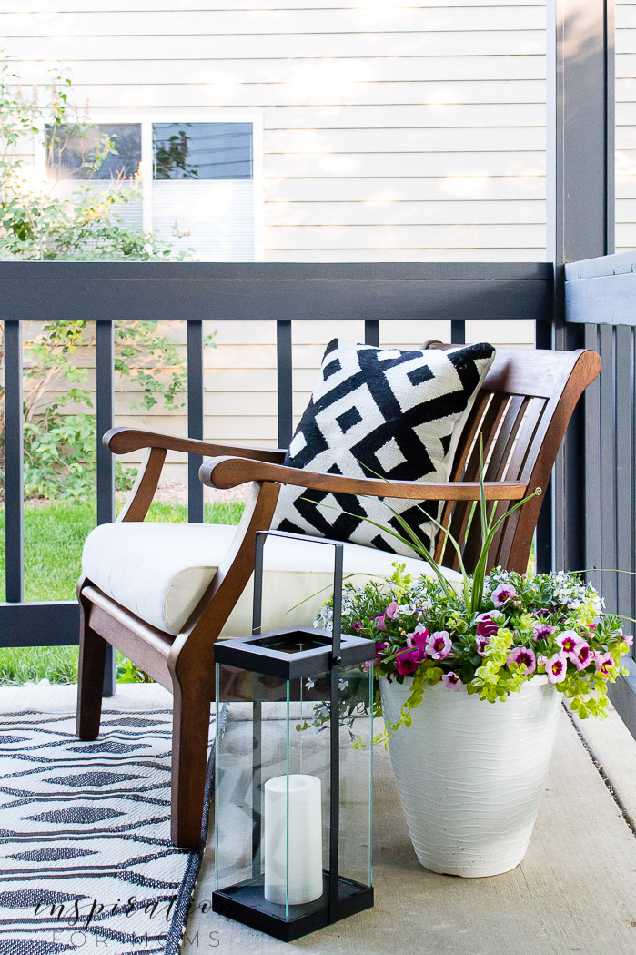 front porch chair with black and white pillow, black lantern
