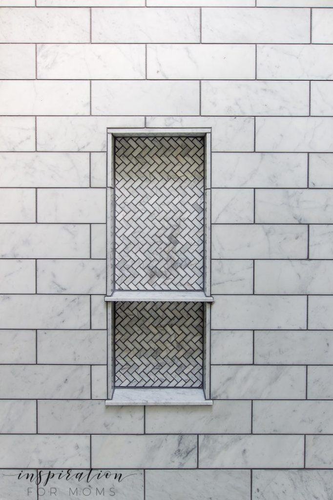 bathroom shower niche with herringbone tile