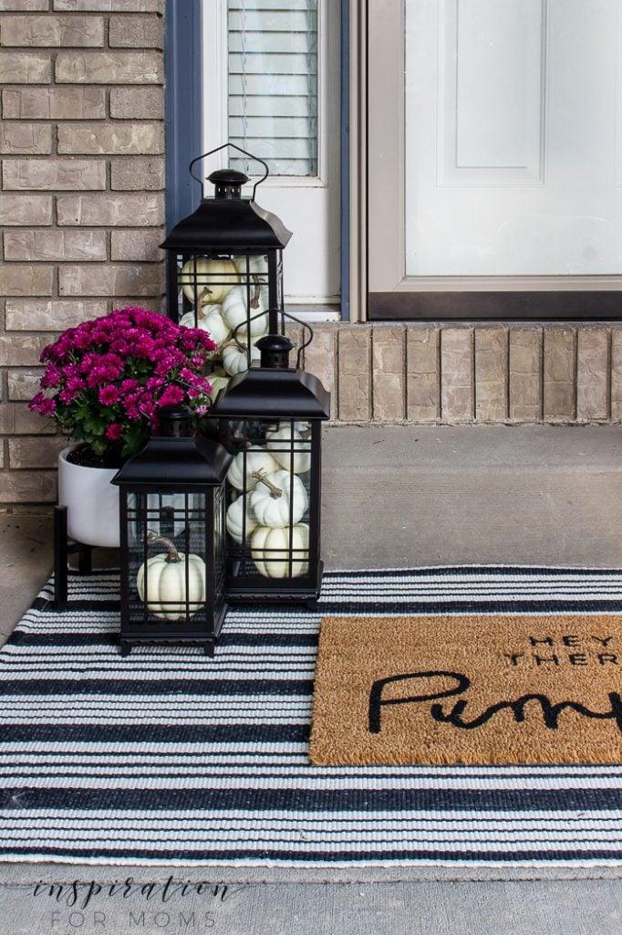fall front door decor, hey their pumpkin doormat, striped rug, black lanterns