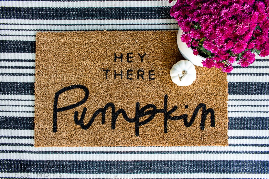 fall home tour - hey there pumpkin doormat on striped rug with plum mum