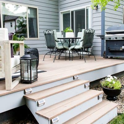 All we needed was one day to give the backyard deck a quick update! Come see how some rocks, paint and a few lights gave new life to a tired deck! #backyarddeck