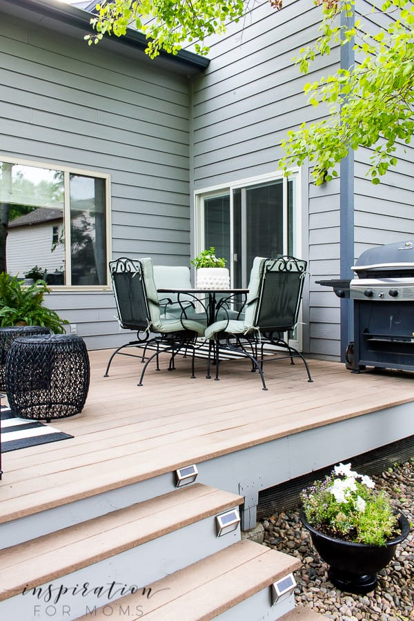 All we needed was one day to give the backyard deck a quick update! Come see how some rocks, paint and a few lights gave new life to a tired deck! #backyarddeck #deckupdate