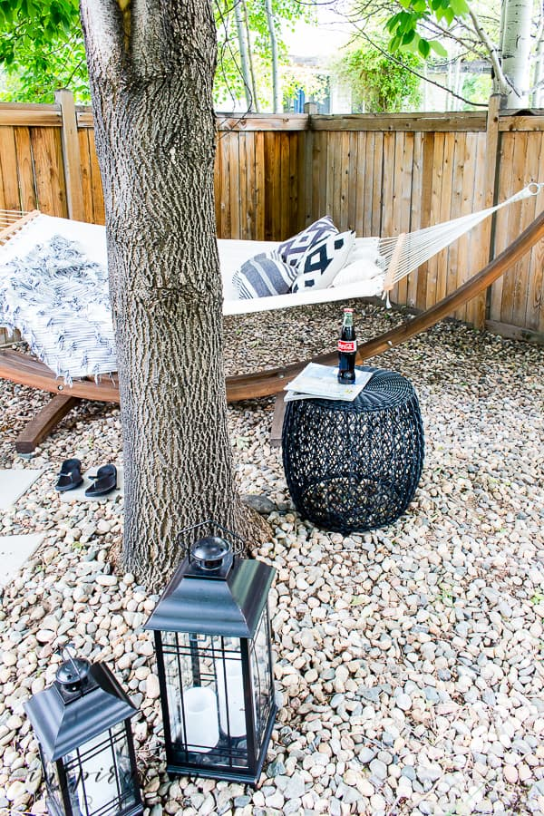 Turn an area of your yard into a backyard hammock oasis escape. It's the perfect way to enjoy the lazy days of summer. #summeroutdoordecor #hammocklife