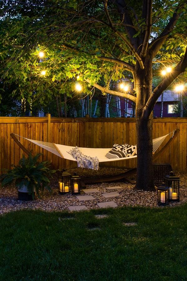 backyard hammock at night with stringed lights through tree and lanterns on ground