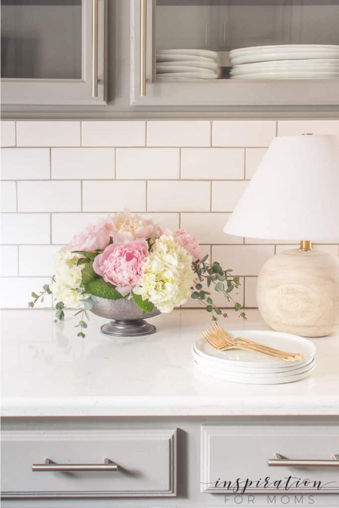 peony and hydrangea arrangement in compote on kitchen quartz counter with wood lamp
