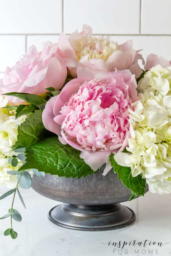 Close up of peony and hydrangea flowers in compote with eucalyptus