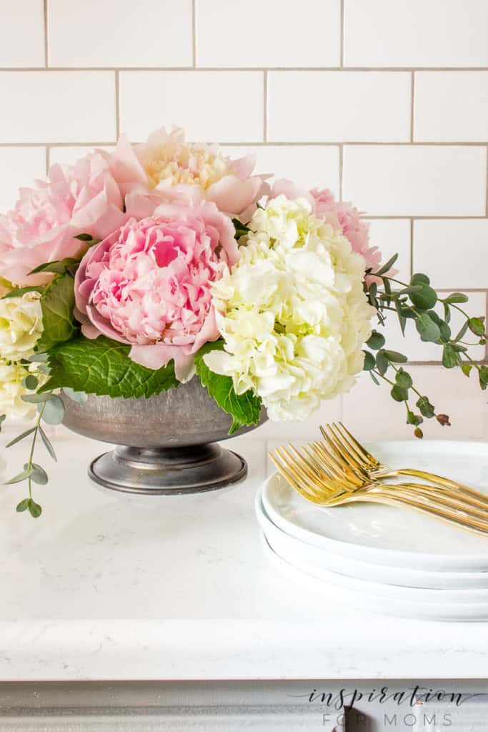 peony and hydrangea arrangement on kitchen counter with white plates and gold forks
