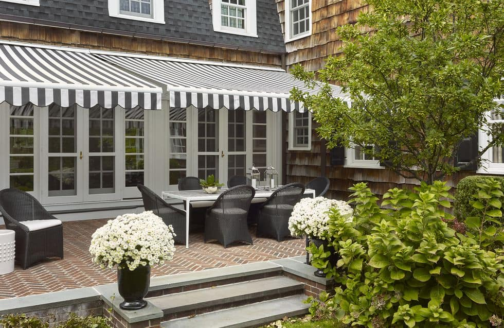 outdoor patio dining area under striped awning metal table with woven chairs