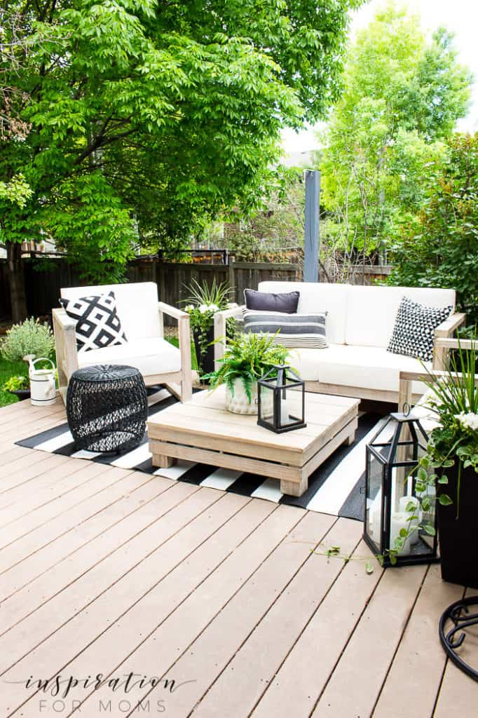 Backyard deck with lounge chairs and black and white striped rug