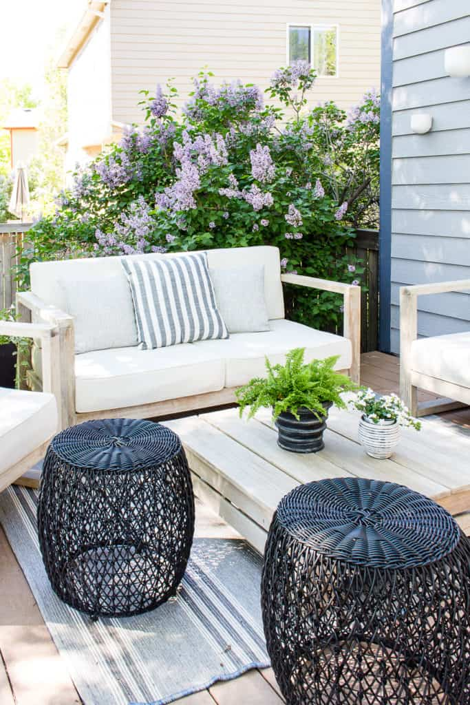 Outdoor deck lounge area with bench and side chairs and black ottomans and lilac in bloom