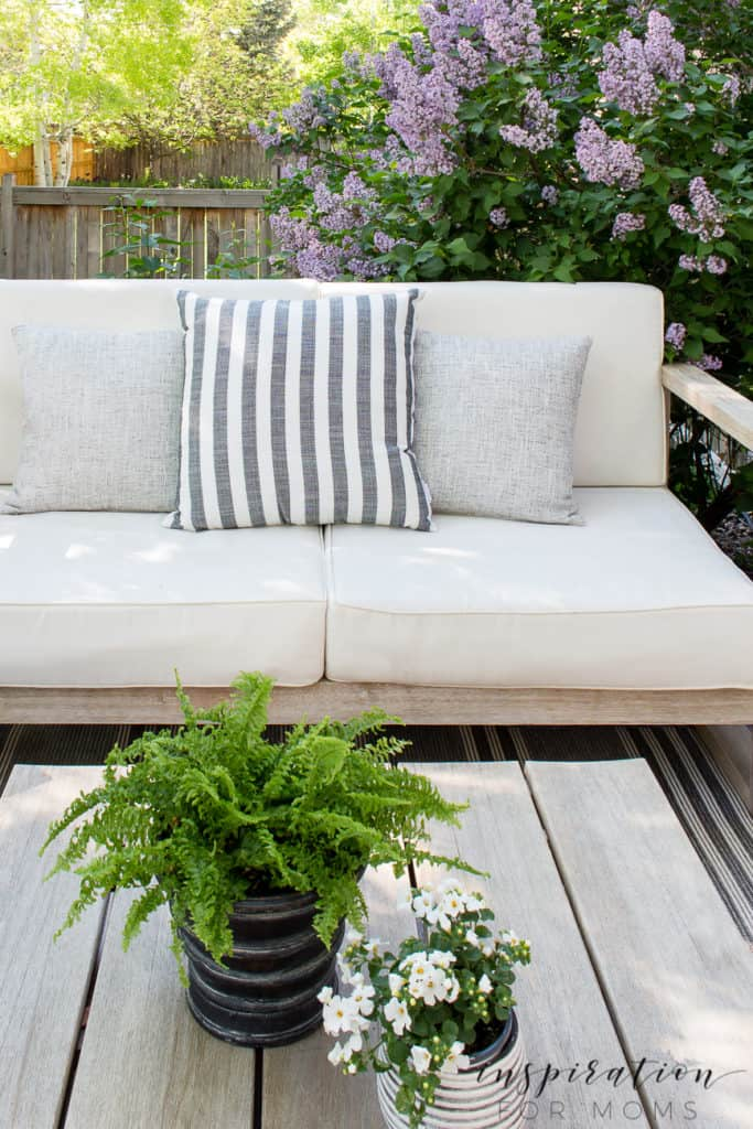Outdoor deck lounge area with bench and lilac in bloom