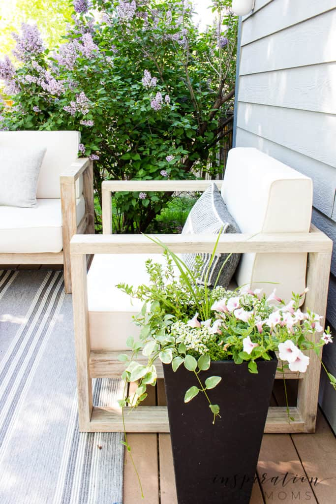 Outdoor deck lounge area with bench and side chairs flower planter and lilac in bloom