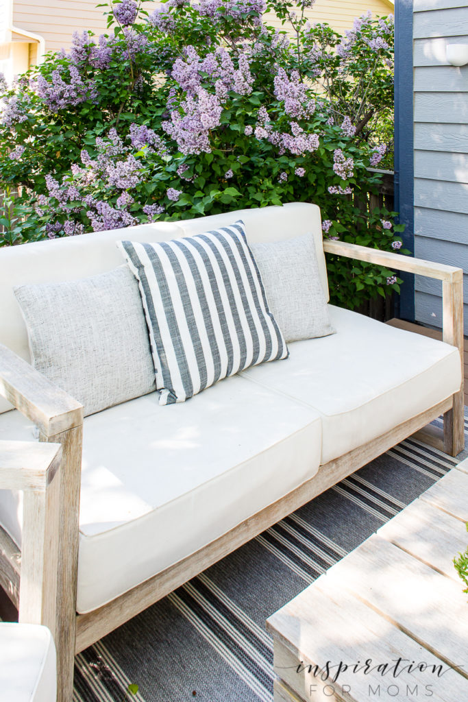 Outdoor deck lounge area with bench outdoor striped pillows and lilac in bloom