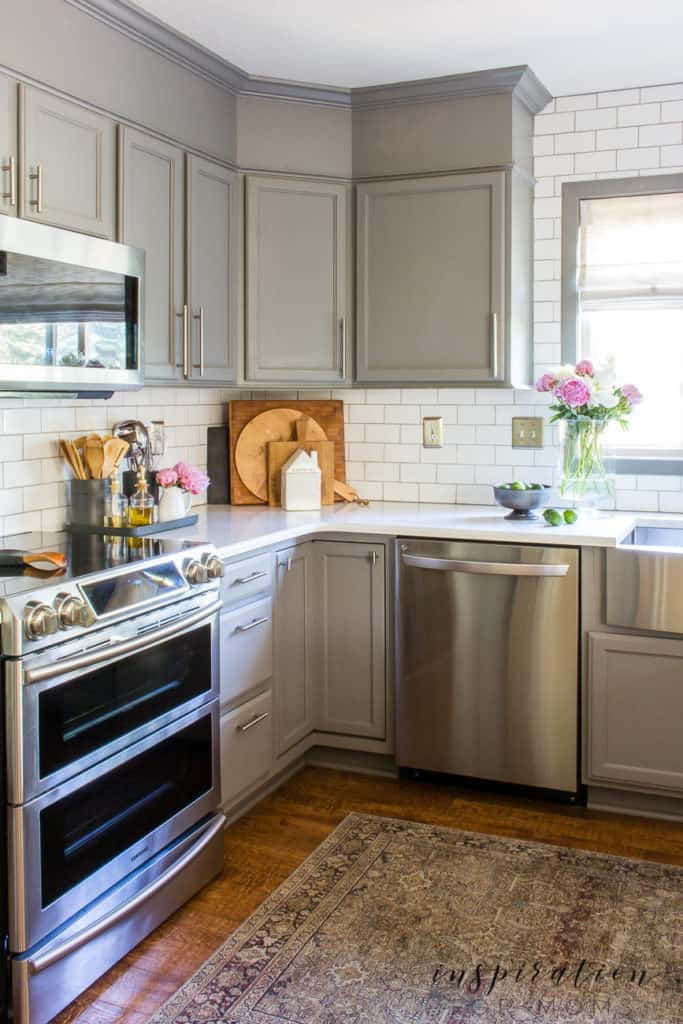 kitchen with white subway tile gray cabinets cooking boards and organized counter tray