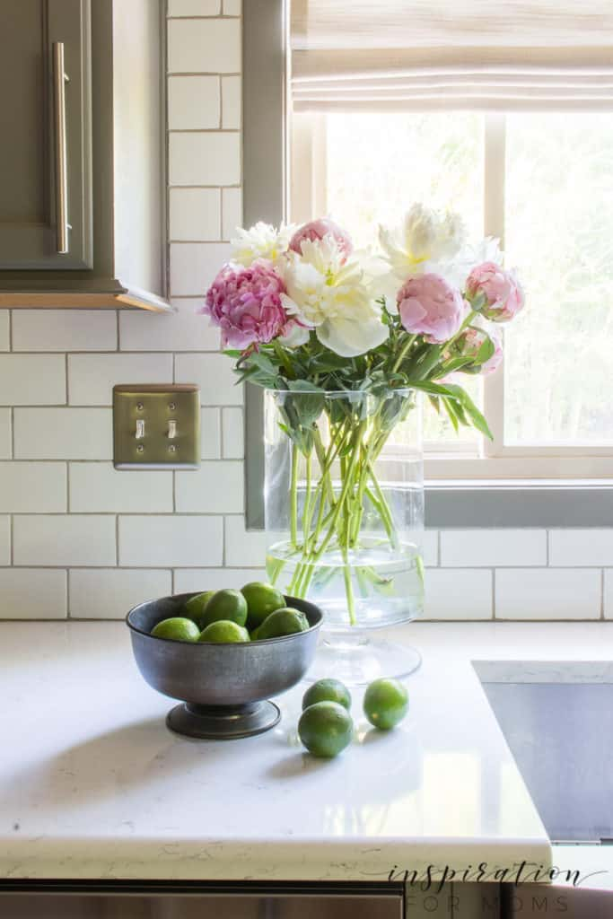peonies in vase with bowl of limes nearby on kitchen counter