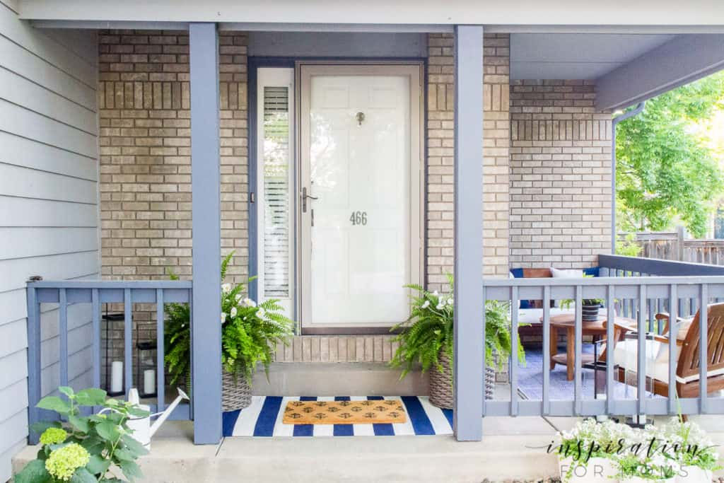 front porch with navy striped rug and layered doormat with Boston ferns flanking front door