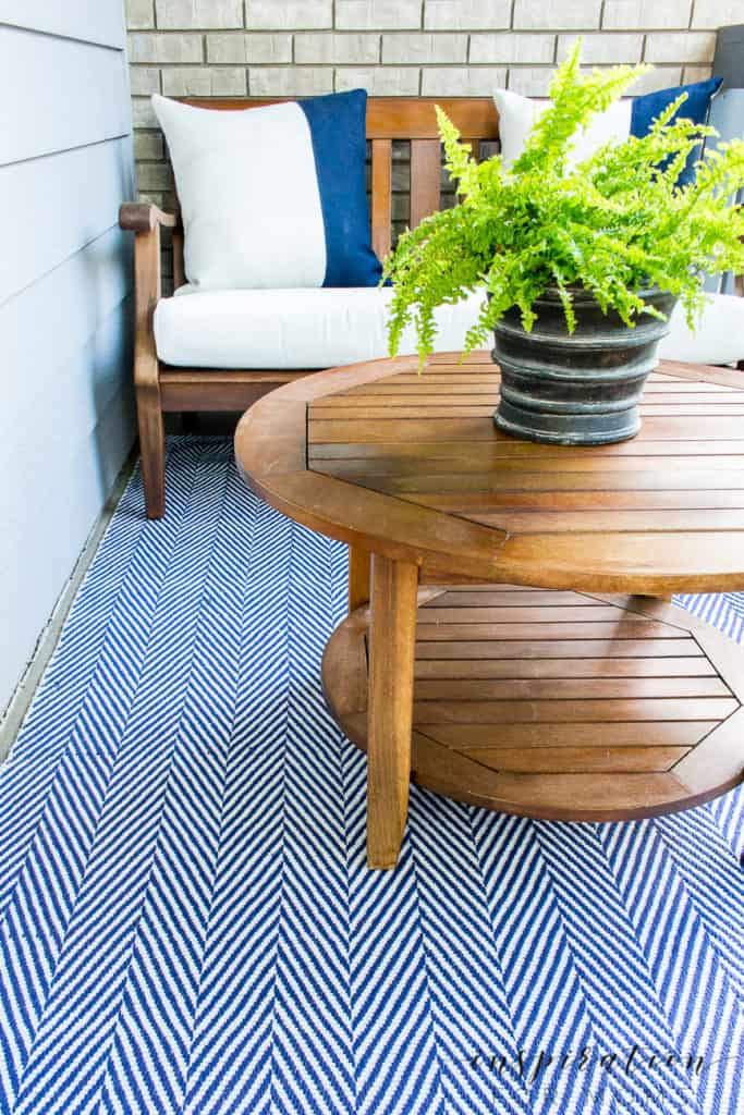 side of front porch seating area with bench two navy striped pillows and coffee table with fern in black garden pot
