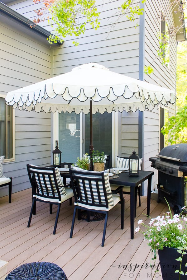 It's summer and everyone wants to live outside. So I've put together some of my best tips for outdoor entertaining! patio dining table with white and black umbrella and seating chairs
