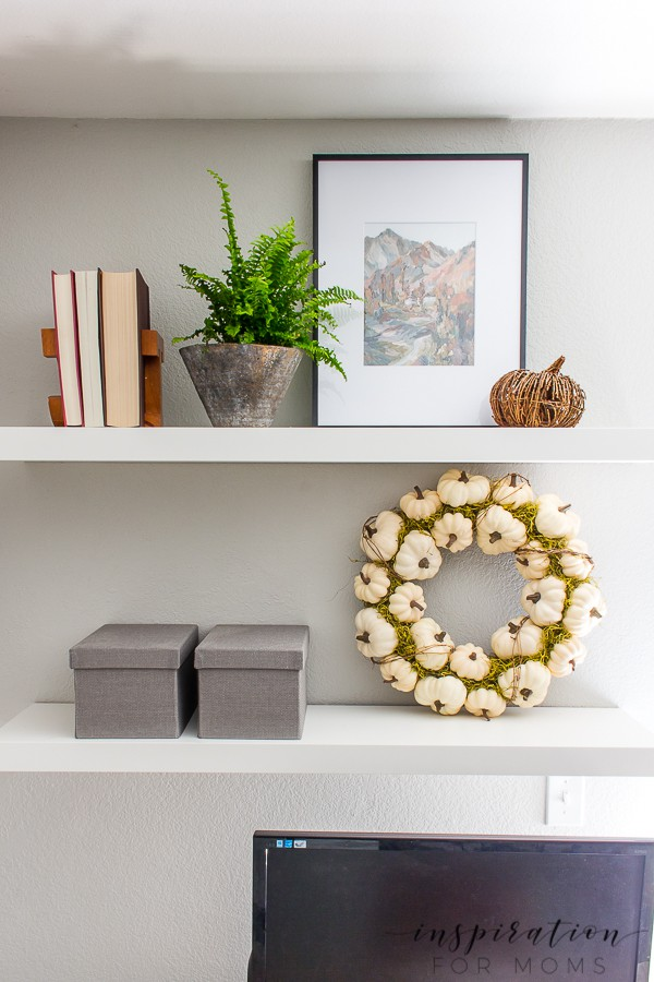 Fall decorated wall shelves with fall prints, white pumpkin wreath and grapevine pumpkins.